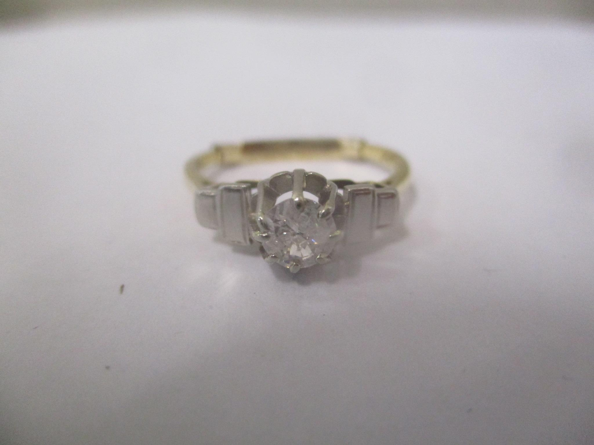 An 18ct yellow gold single stone ring with a platinum head and shoulders, claw set with a