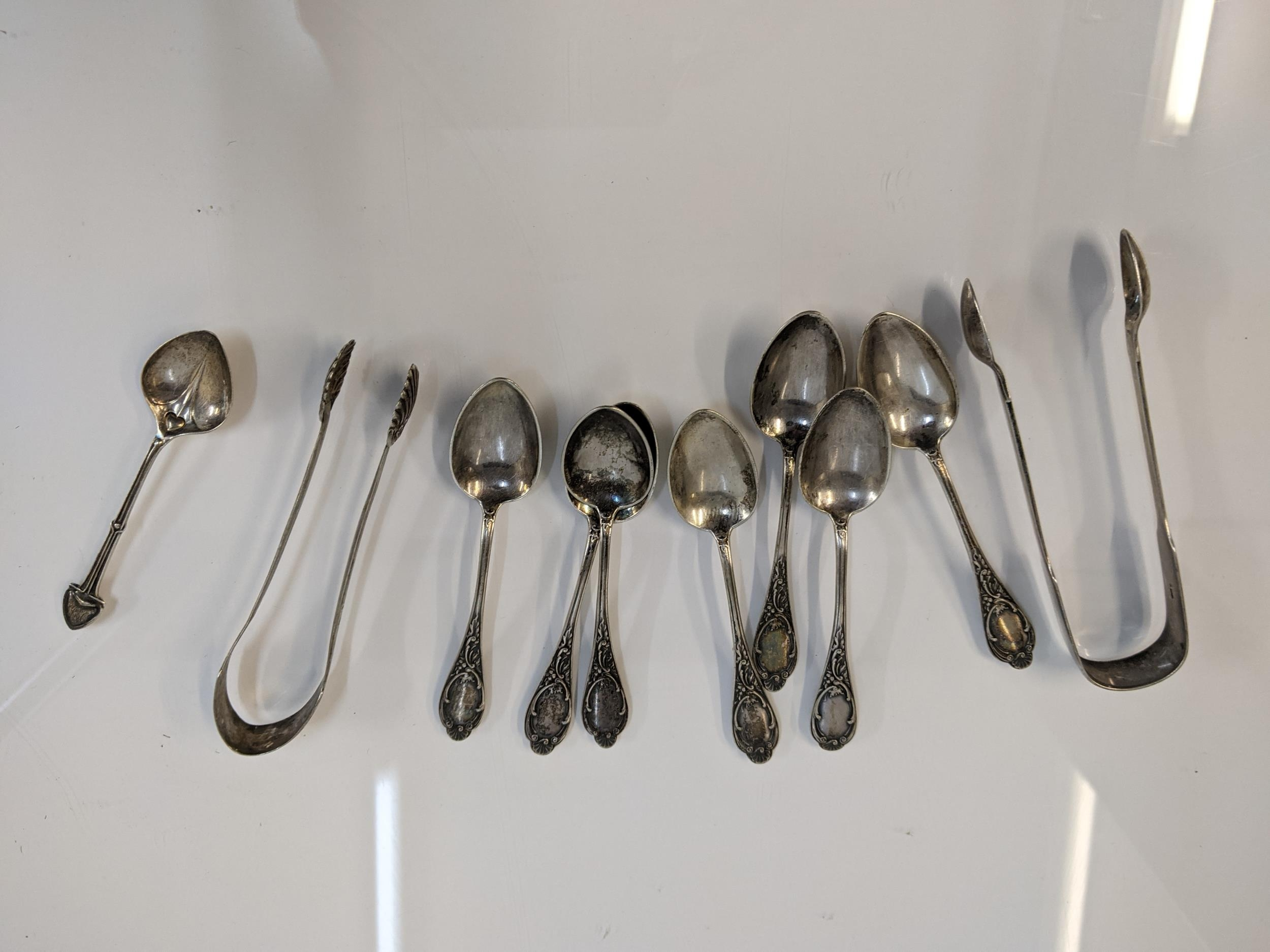 Silver and silver coloured metal to include seven teaspoons stamped 800, two sugar tongs and a