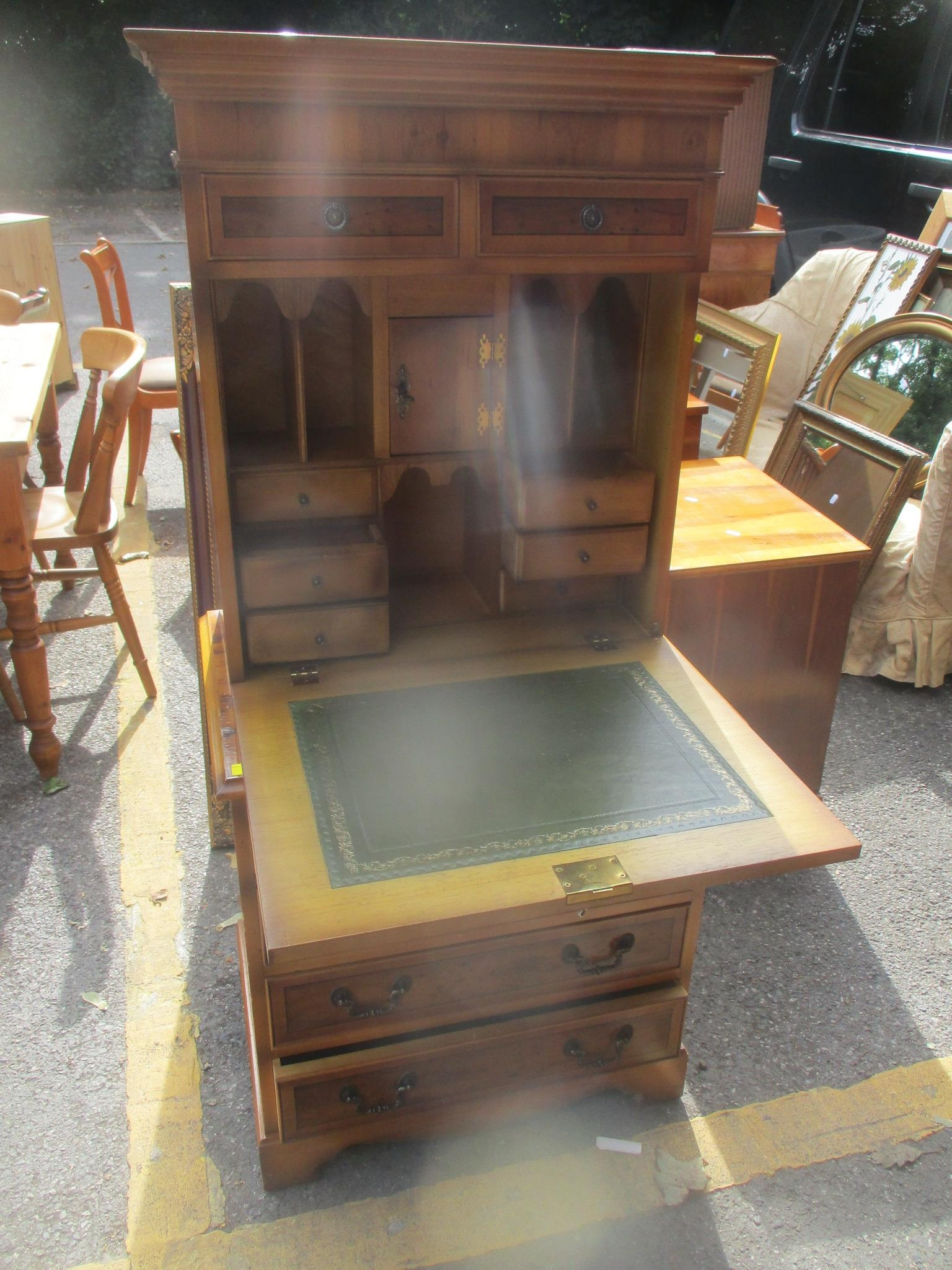 A reproduction yew wood cabinet/writing desk having a fall flap revealing fitted interior and a