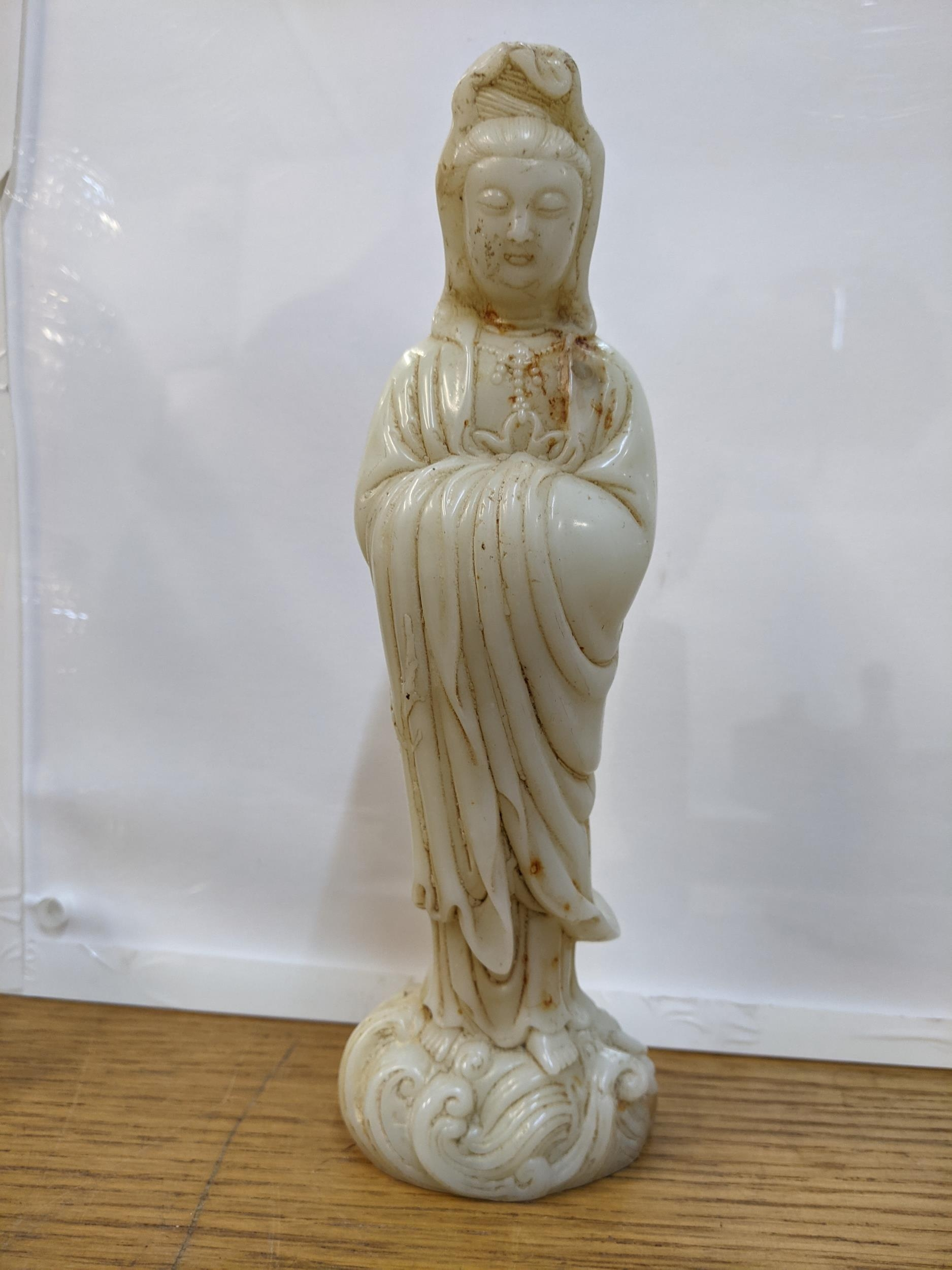 A Chinese off white jade coloured statue of a woman on a wave design base 24cm high