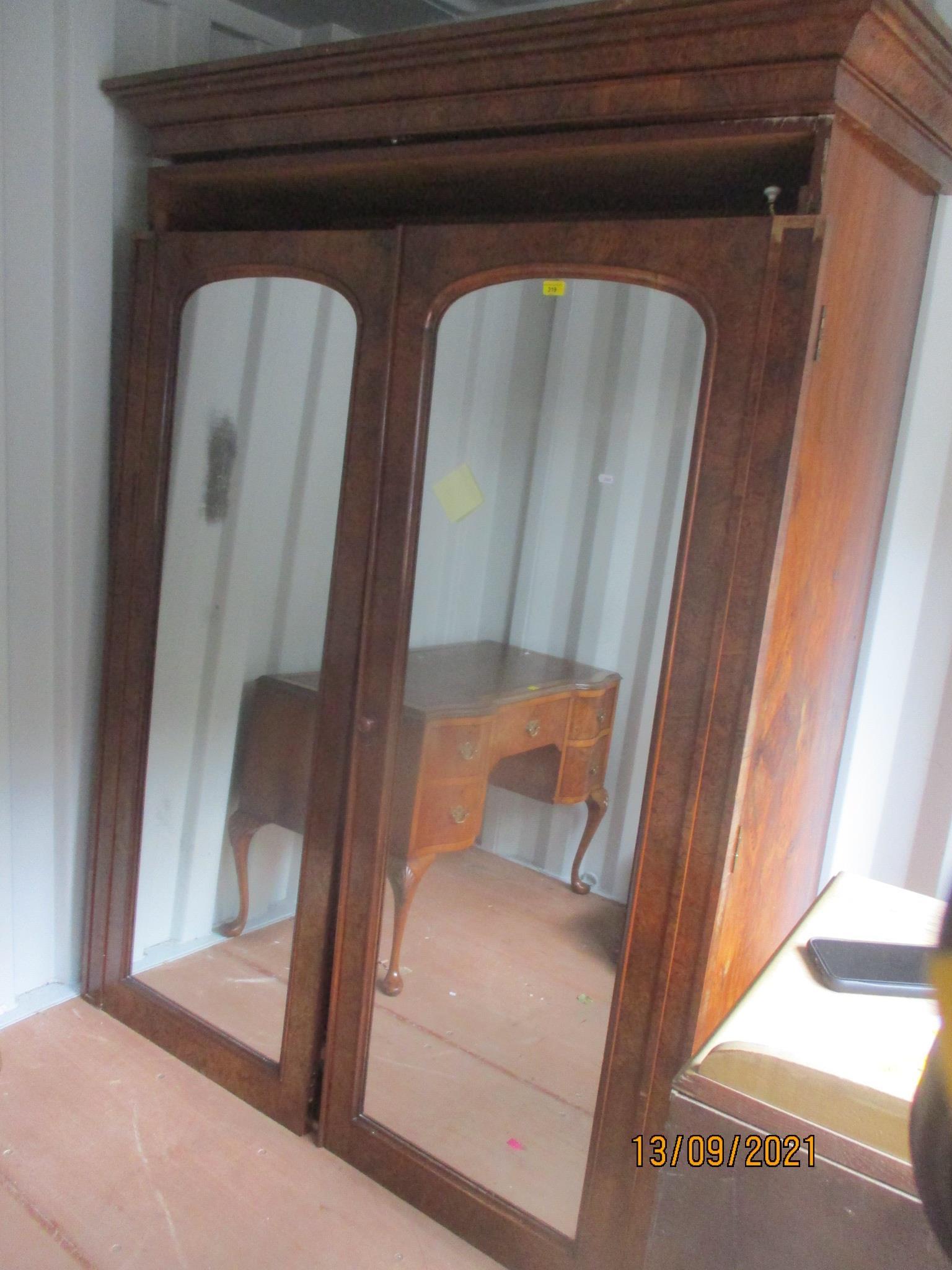 A Victorian burr walnut veneered two door wardrobe having two mirrored doors, revealing filled