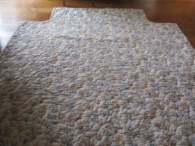 A Colefax and Fowler kingsize quilted bed cover having a white background with sprays of blue and