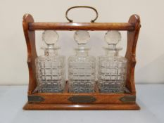 An early 20th century oak three bottle tantalus with original decanters and key Location: RWM