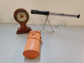 An Edwardian inlaid mahogany balloon shape clock, together with a miniature telescope on stand