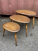 A nest of three mid 20th century Ercol dark stained elm and beechwood 'Pebble' occasional tables,