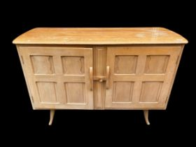 A mid century Ercol light elm sideboard, with two carved doors enclosing two drawers and shelf