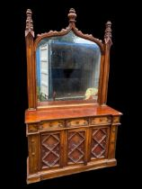 A Victorian walnut Gothic style mirrored backed sideboard, the mirror supported by two carved