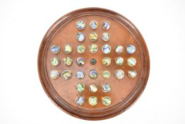 A late 19th century mahogany solitaire board with 32 handmade marbles