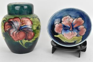 A Moorcroft Hibiscus ginger jar by Walter Moorcroft on a green ground 15cm high together with a