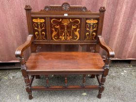 An Art Nouveau mahogany two seater bench having marquetry floral inlaid panels, scrolled shaped arms