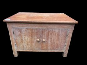 Attributed to Heals a 1950s limed oak small cupboard having two cupboard doors and standing on block