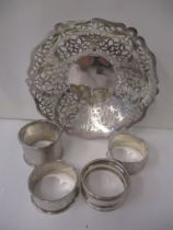 Four silver napkin rings and a silver dish with pierced decoration, 157g