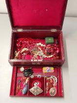 A collection of costume jewellery together with a red leather jewellery box Location: port