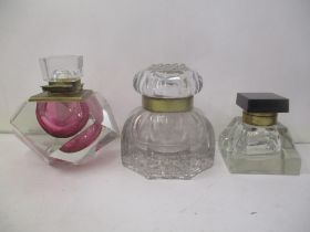 Three late 19th/early 20th century glass inkwells with a brass hinged collar