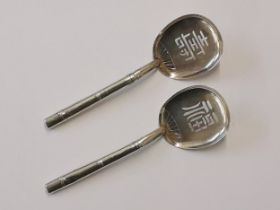 A pair of Chinese silver spoons in the form of fans with bamboo handles, stamped sterling 950,