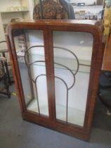 An Art Deco walnut veneered display cabinet having twin glazed doors and two loose glass shelves,