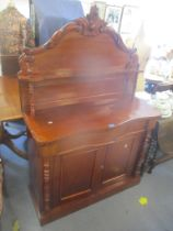 A Victorian mahogany chiffoniere having a carved, raised top, serpentine front and drawer above twin