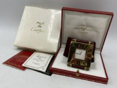 A Cartier quartz folding bedside/travel alarm clock having a white dial in a brass case with