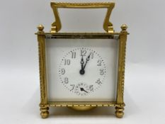 An early 20th century square formed alarm carriage clock, the white enamel dial having Arabic