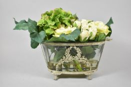 A Reproduction French Style Oval Glass Planter with White Metal Surround and Containing Artificial