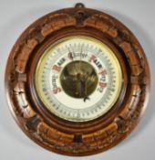 An Edwardian Wall Hanging Circular Carved Oak Aneroid Barometer, 21cm Diameter
