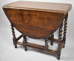 A Mid 20th Century Oak Barley Twist Oval Topped Drop Leaf Gate Legged Dining Table