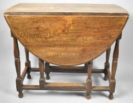 A Mid 20th Century Oak Drop Leaf Oval Topped Gate Legged Dining Table