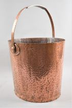 A Hand Beaten and Riveted Copper Bucket with Loop Handle of Oval Form, 28cms Long and 25cms High