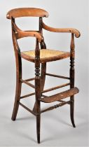 An Edwardian Cane Seated Child's High Armchair with Footrest, 84cm high
