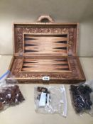 A VINTAGE DECORATIVE CARVED WOOD SUITCASE CHESS AND BACKGAMMON GAME SET