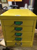 A YELLOW METAL FIVE DRAWER FILING CABINET