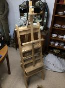 AN UNUSUAL WOODEN FOLDING EASEL WITH PAINT HOLDING SHELVES, 163CM