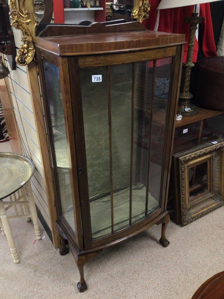 A VINTAGE DISPLAY CABINET WITH A BOW FRONTED GLASS DOOR ON BALL AND CLAW FEET, WITH GREEN VELVET