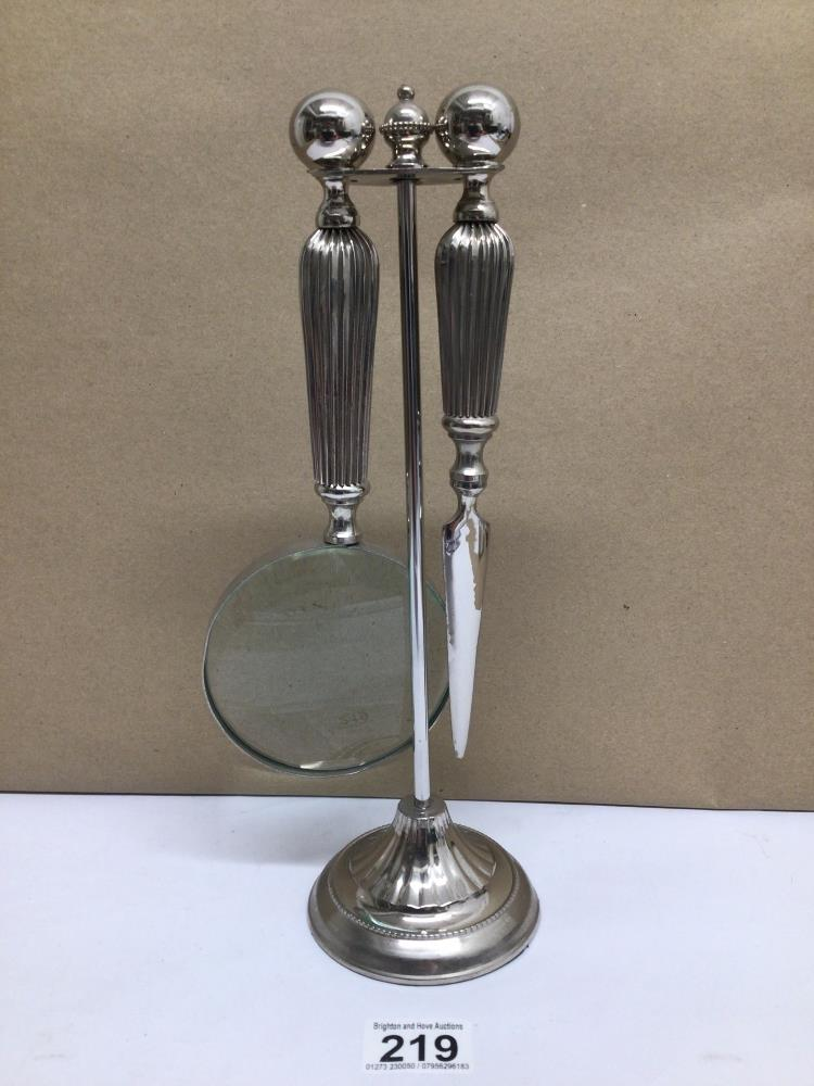 A WHITE METAL SET OF MAGNIFYING GLASS AND LETTER OPENER ON STAND
