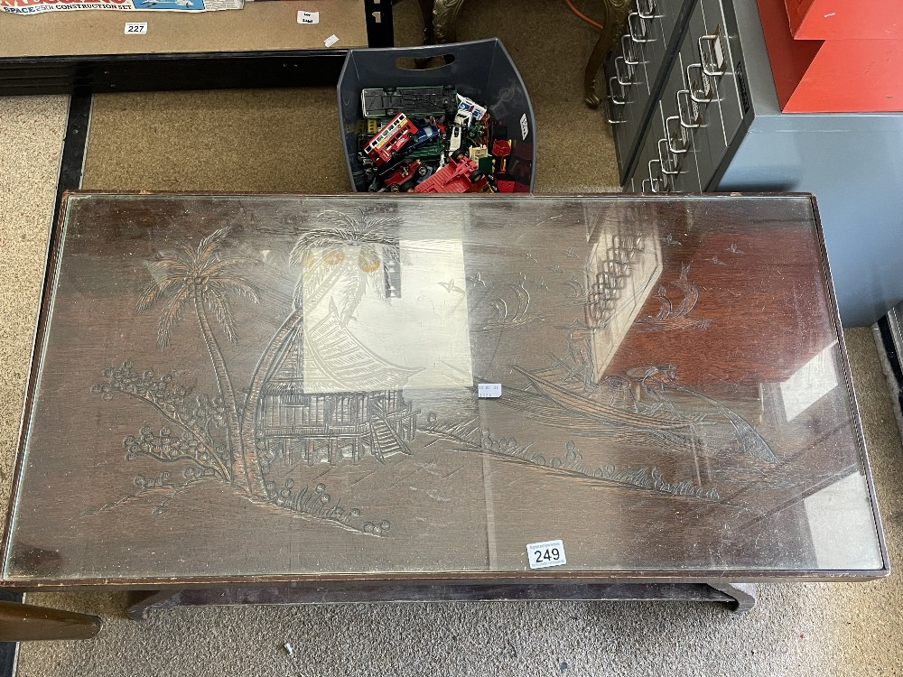 A CARVED WOODEN GLASS TOP TABLE OF ORIENTAL DESIGN 2-TIER COFFEE TABLE, 93CM X 47CM X 46CM