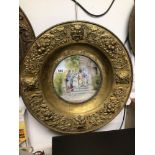 AN EARLY BRASS SURROUND WALL MOUNTED HANDPAINTED CERAMIC CHARGER, 59CM DIAMETER