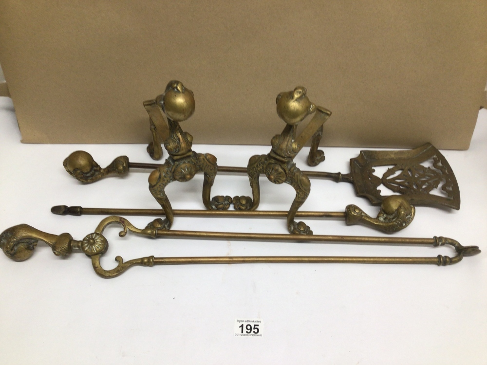 A VINTAGE BRASS BALL AND CLAW MOTIF FIRE COMPANION SET WITH A PAIR OF FIREDOGS TO MATCH