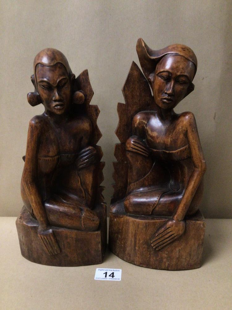 A PAIR OF PITA MAHA STYLED BALINESE CARVED WOODEN FIGURES/BOOKENDS