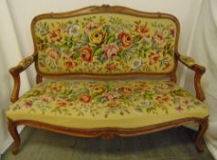 An upholstered settle with tapestry back, seat and arms on cabriole legs