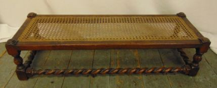A rectangular oak foot stool with bergere top and barley twist stretchers, 23 x 91 x 33cm