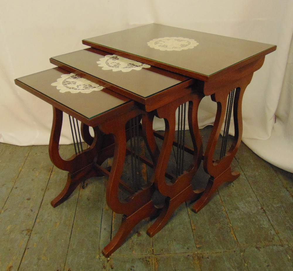 A nest of three rectangular mahogany side tables with glass tops, lyre sides with scroll supports,