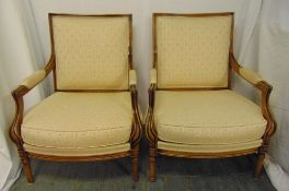 A pair of continental upholstered armchairs with scrolling yew wood arms on turned legs