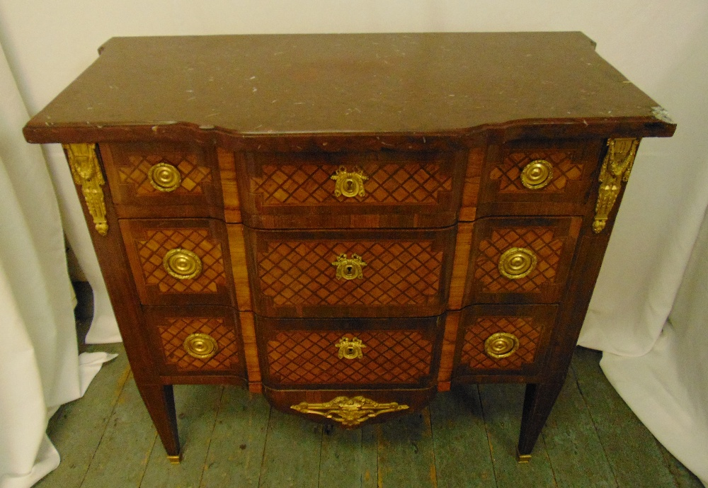 A French 19th century Louis XVI style chest of drawers with red marble top and gilded mounts on four