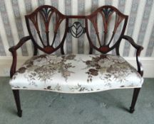 An Edwardian two seater settle with upholstered seat, pierced shield backs, scrolling arms on four