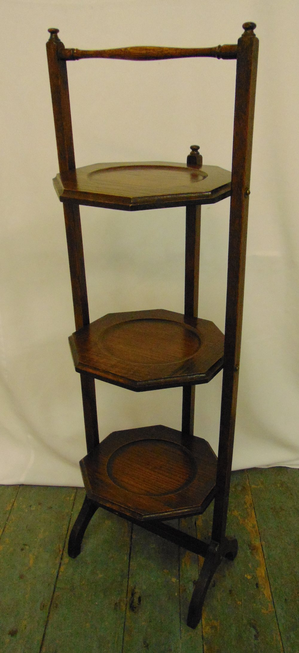 An oak three tier plate stand of customary form, 91cm (h)