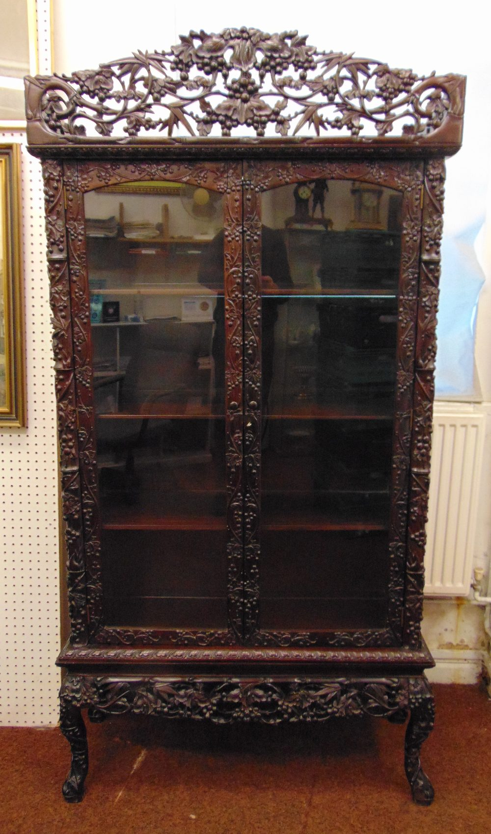A Chinese rectangular hardwood glazed double door display cabinet, profusely carved and pierced with