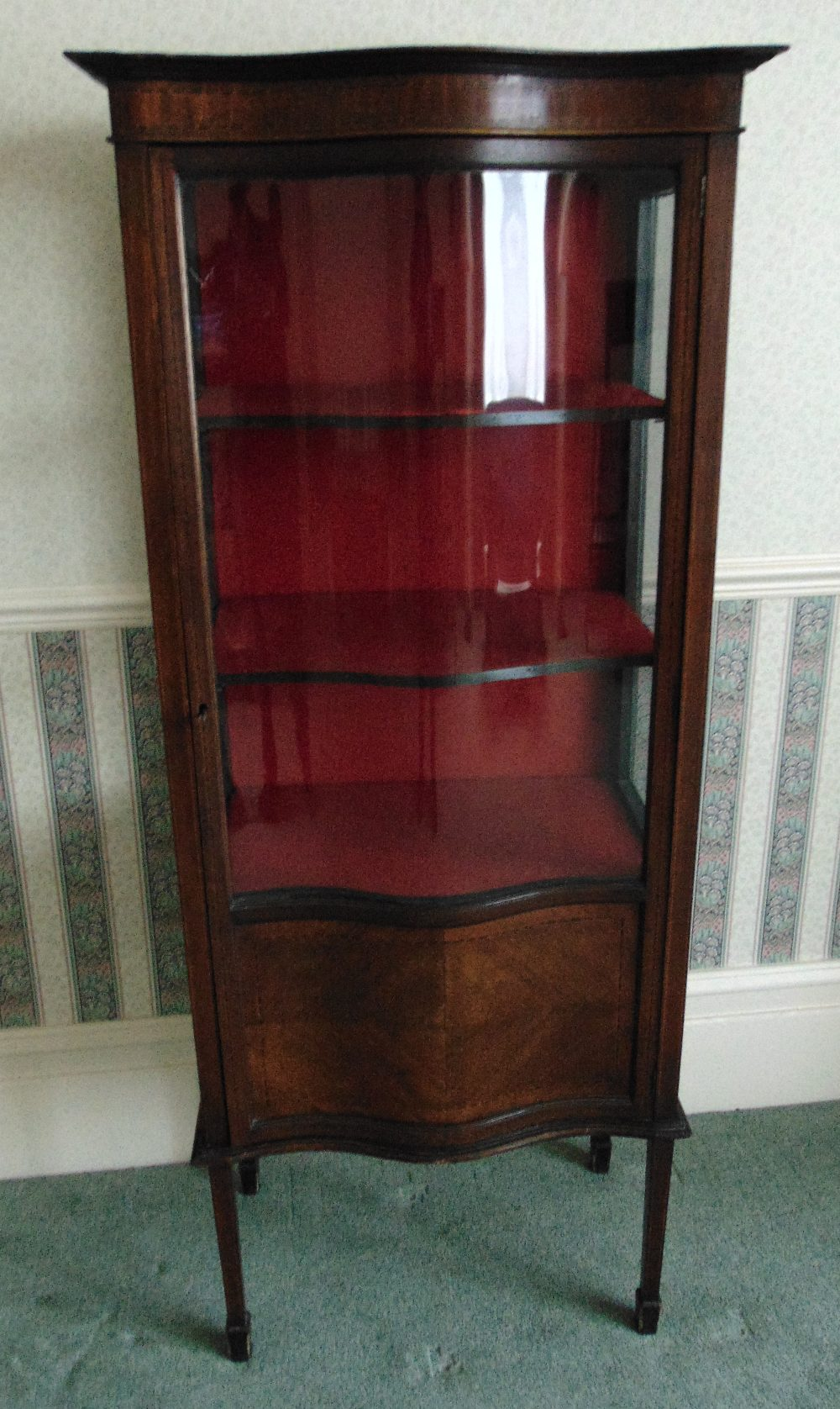 An Edwardian mahogany glazed display cabinet with bow fronted hinged glass door and satinwood inlays