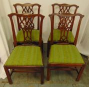 Four mahogany dining chairs with scroll pierced backs, upholstered seats on four rectangular legs