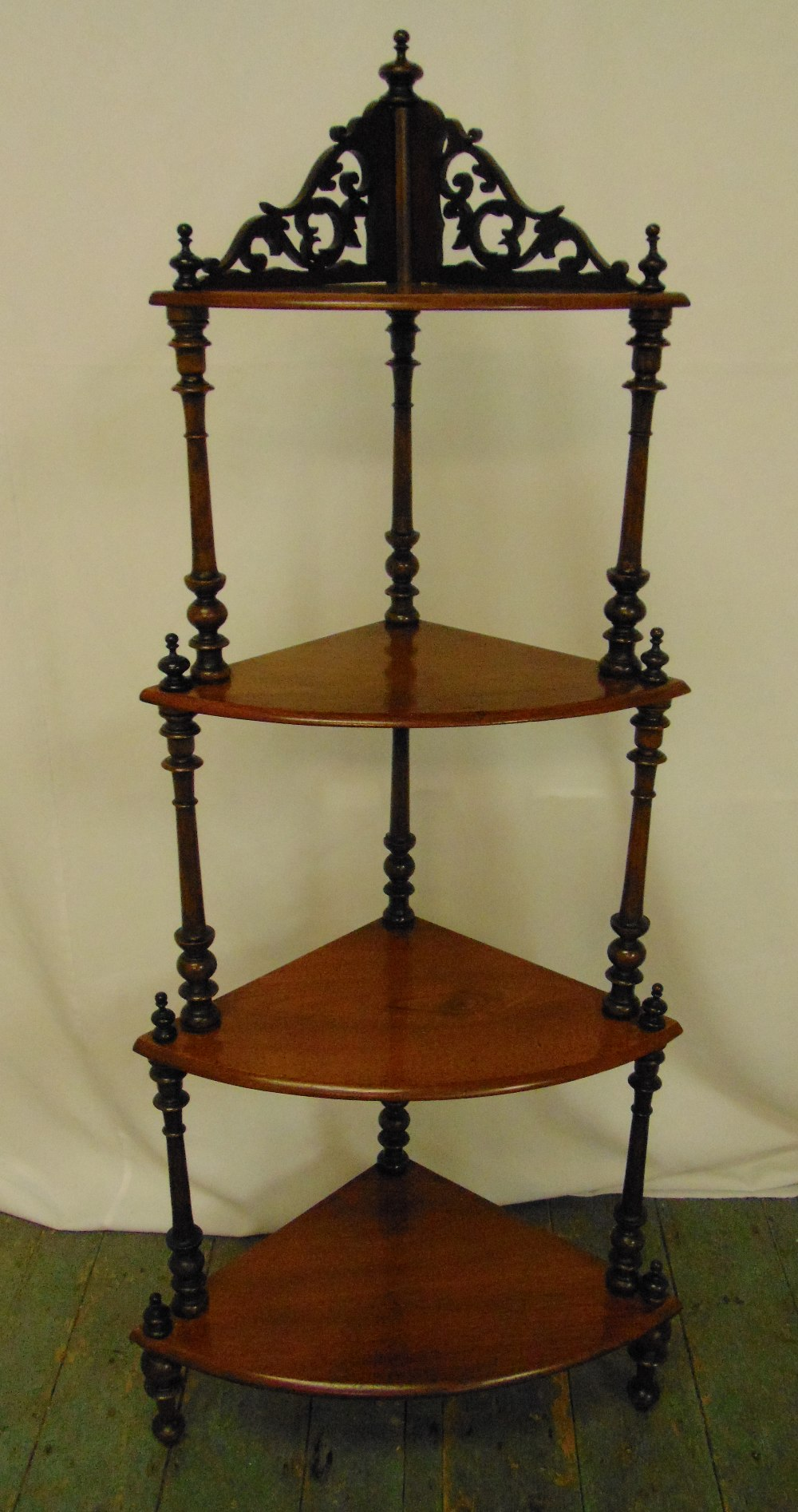 A Victorian mahogany four tier corner whatnot, scroll pierced with turned column supports on three