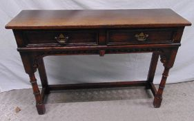 A 19th century oak consol table with two drawers with hinged swing handles, 76 x 106.5 x 30cm